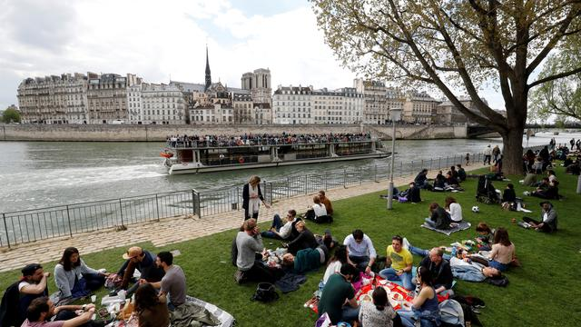 "People sit on the grass during the official launch of the ""Rives de Seine"" (Seine's banks) park on the banks of the River Seine in Paris on April 2, 2017. The right bank of the Seine, whose 3.3km banks are classified as Unesco World Heritage, is officially prohibited to cars since October 21, 2016. / AFP PHOTO / FRANCOIS GUILLOT"