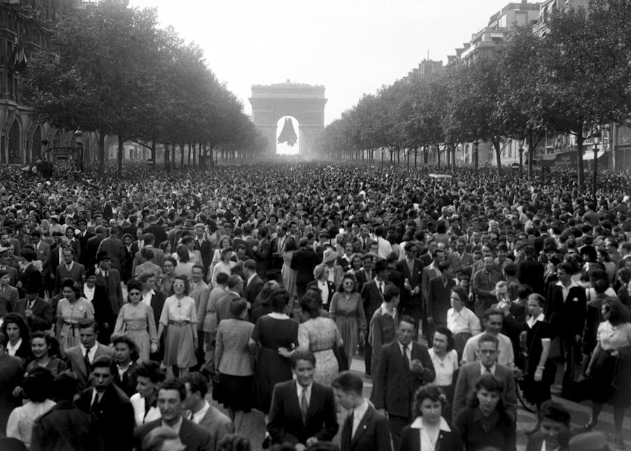 Picture dated of May 8, 1945 showing people gathering at the Champs Elysees Avenue, in front of the Triumphal Arch (Arc de Triomphe) as Parisians celebrate the unconditionnal German capitulation in the streets of Paris, at the end of the second World War.